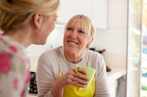 Mother and daughter talking, drinking coffee in kitchen